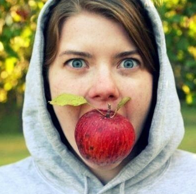 Heather with apple in mouth wearing hoodie