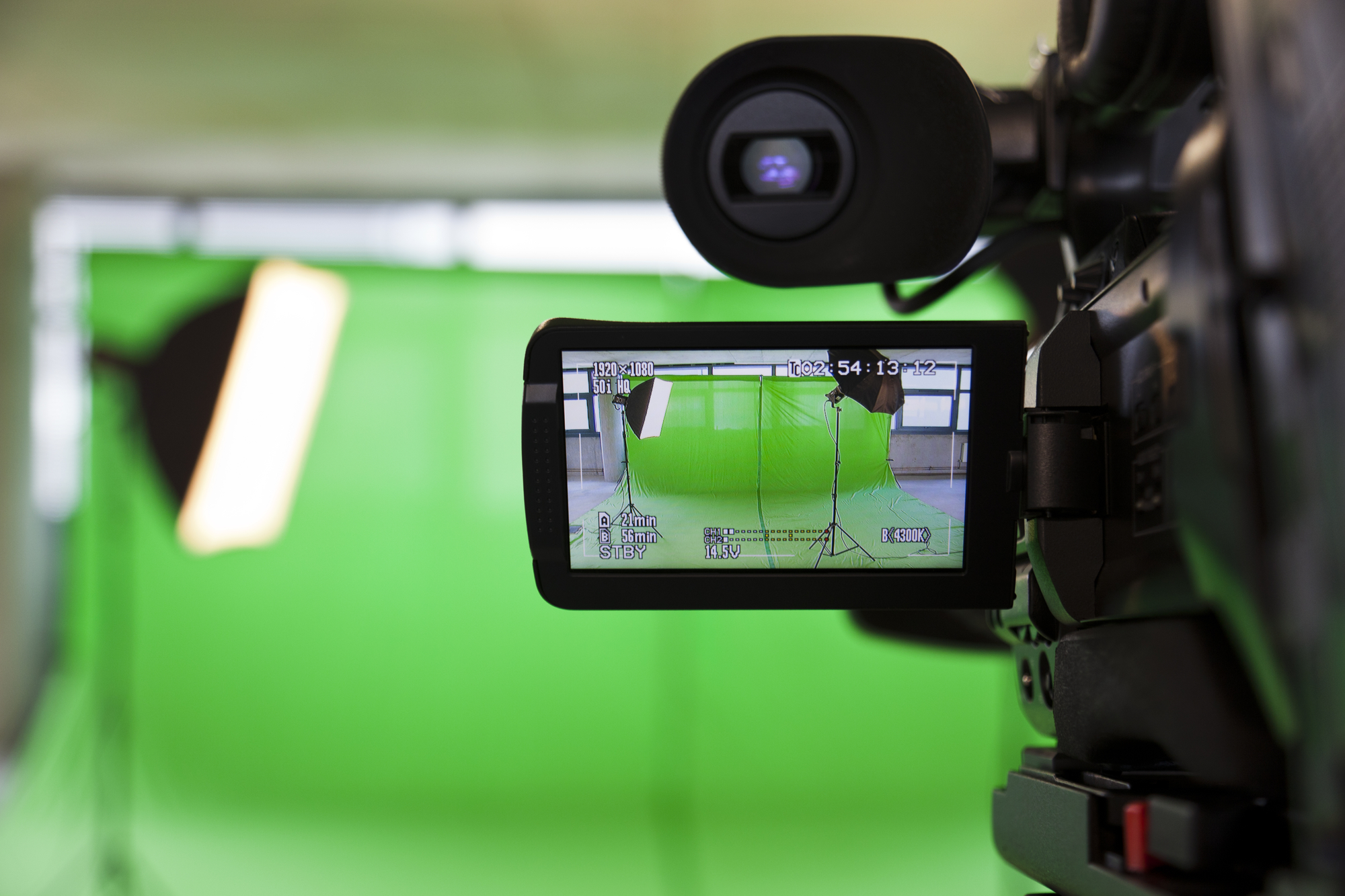 Viewfinder of video camera looking at green screen set