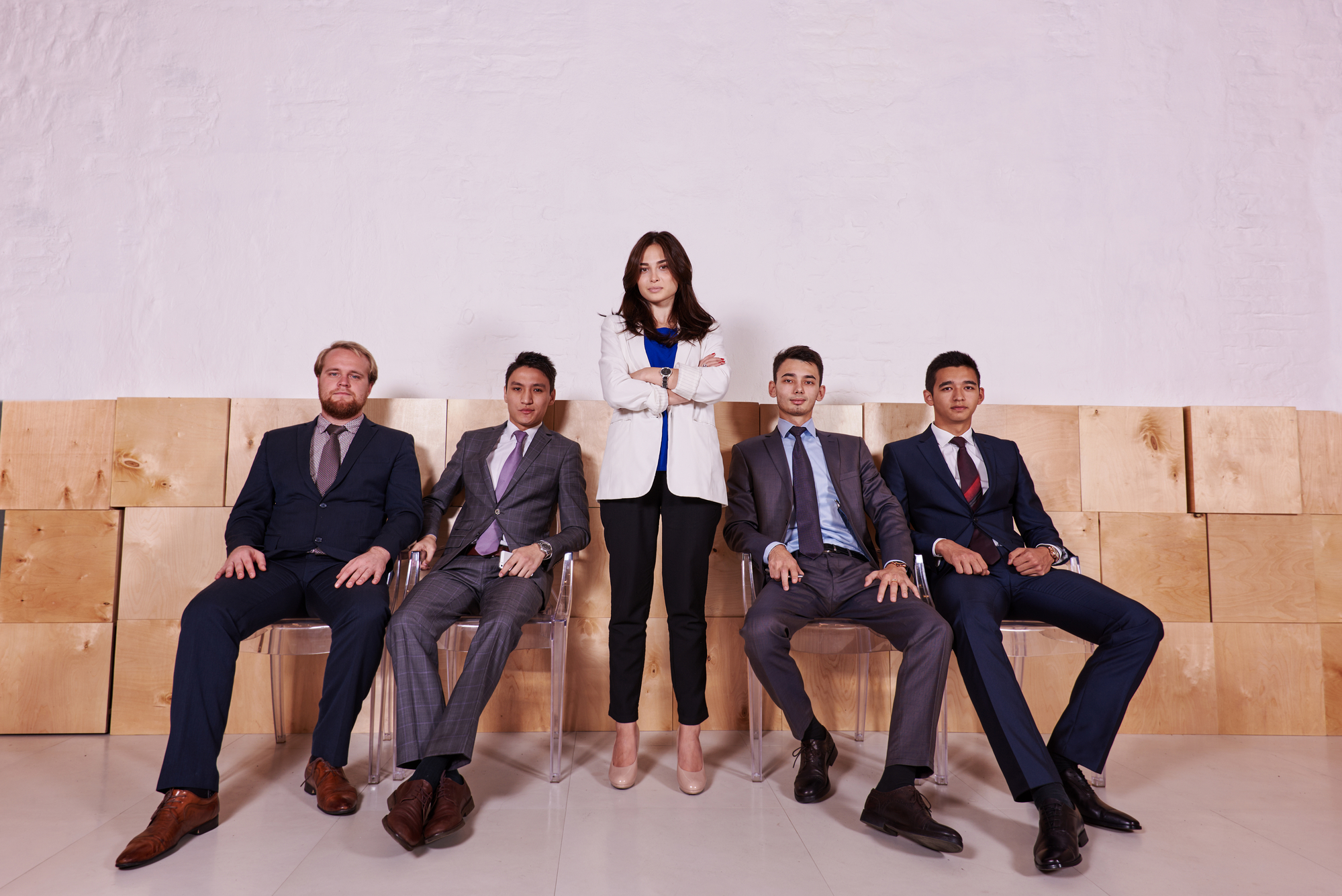 Full length portrait of a group of a successful leadership dressed in corporate clothes posing inside, confident colleagues in formal wear resting after briefing while sitting in hallway