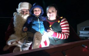 A familiar santa and elf pose with child in sleigh outside Transformation Marketing's office building